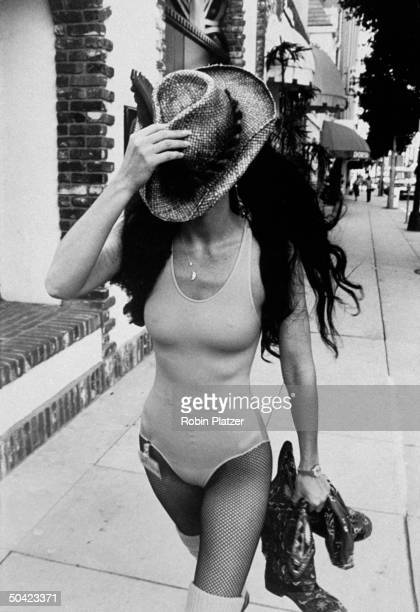 Singer Cher wearing leotard and fishnet stockings covering face w straw hat while shopping in Beverly Hills CA