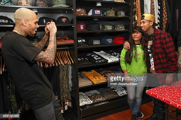 Singer Chris Brown takes a photograph of a fan posing with rapper Tyga at the 1st Annual Xmas Toy Drive hosted by Chris Brown and Brooklyn Projects...