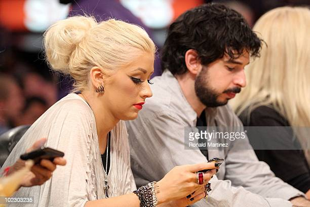 Singer Christina Aguilera and husband Jordan Bratman look at their phones from their courtside seats during Game Seven of the 2010 NBA Finals at...
