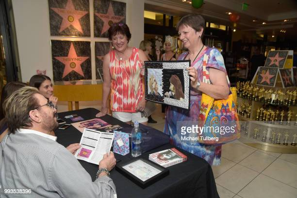 Singer Chuck Negron receives fan art from a fan at the unveiling party for his new candy line at Sweet! Hollywood Boutique on July 7, 2018 in...