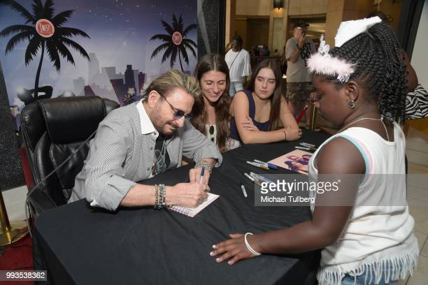 Singer Chuck Negron signs an autograph for a fan at the unveiling party for his new candy line at Sweet! Hollywood Boutique on July 7, 2018 in...