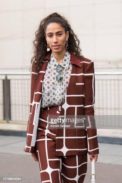 Singer Ciinderella Balthazar wears a Furla bag, Guy Laroche suit and a Cerruti shirt on February 26, 2020 in Paris, France.