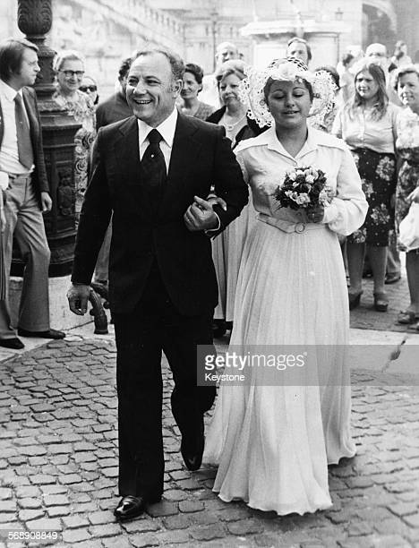 Singer Claudio Villa and his new wife Patrizia Baldi walking past crowds of people as they leave the church following their wedding 1970