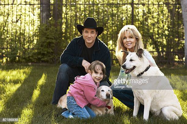 Singer Clint Black poses for a portrait session for People Magazine with his actress/wife Lisa Hartman Black their daughter Lily and dogs Sunny and...