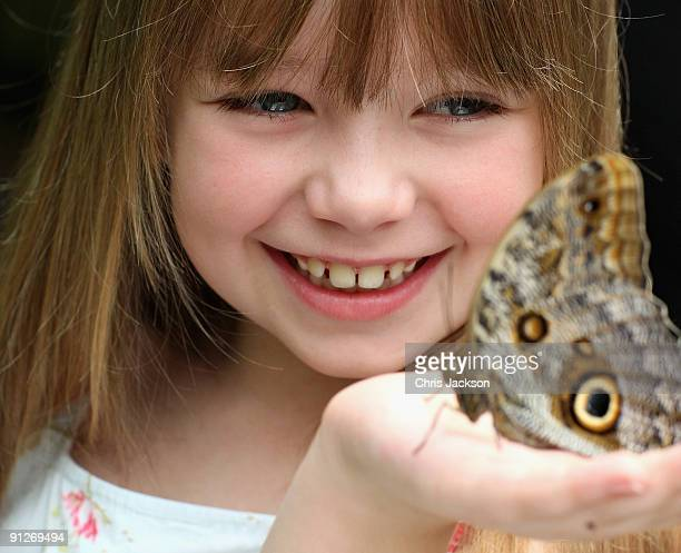 Singer Connie Talbot looks at a butterfly as she takes part in a photoshoot at London Zoo on June 25 2009 in London England