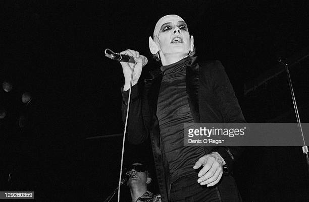 Singer Dave Vanian performing with English punk group The Damned in false pointed ears and a bald wig circa 1978
