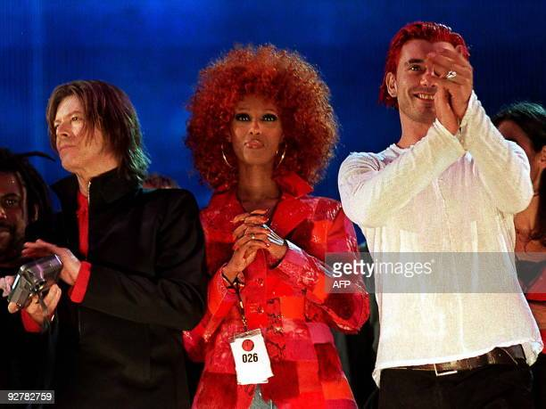 Singer David Bowie is joined by wife Iman and Bush guitarist Gavin Rossdale on stage at the end of the NetAid charity concert in Wembley stadium late...