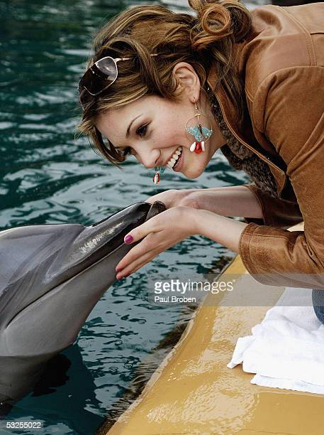 Singer Delta Goodrem plays with dolphins at Sea World on July 19 2005 in Main Beach Gold Coast Australia