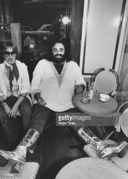 Singer Demis Roussos interviewed at a cafe for the BBC television show 'The Roussos Phenomenon' Champs Elysees Paris May 1976 First printed in Radio...
