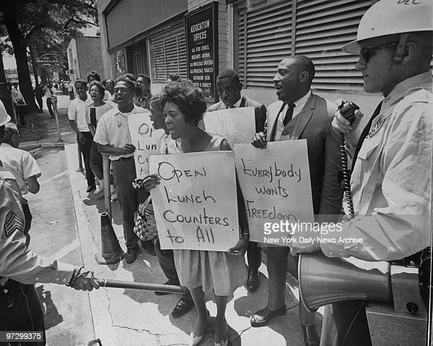Singer Dick Gregory holds sign reading 'Everybody wants Freedom' as he leads demonstrators to jail while police look on in Birmingham Ala