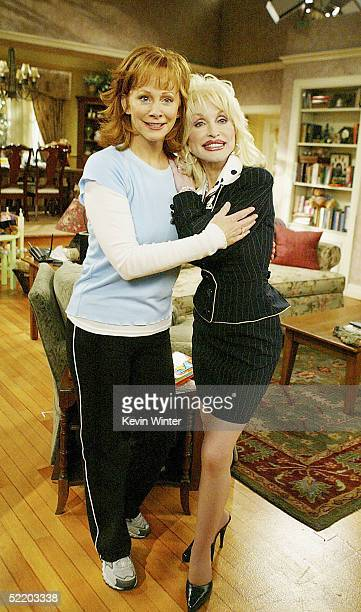 Singer Dolly Parton and Reba McEntire pose on the set of The WB's Reba at 20th Century Fox Studios on February 15 2005 in Los Angeles California
