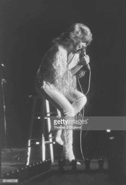 C/W singer Dottie West singing into mike as she sits on high stool during performance on stage at the Chicago Amusement Park