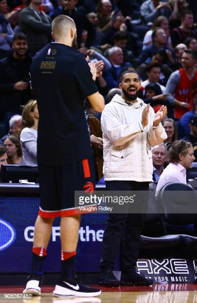 Singer Drake applauds with Jonas Valanciunas during the second half of an NBA game against the Golden State Warriors at Air Canada Centre on January...