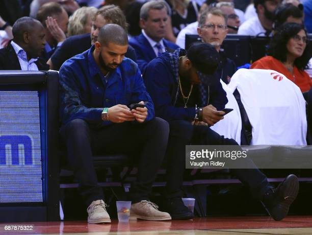 Singer Drake checks his mobile phone in the first half of Game Three of the Eastern Conference Semifinals between the Toronto Raptors and the...