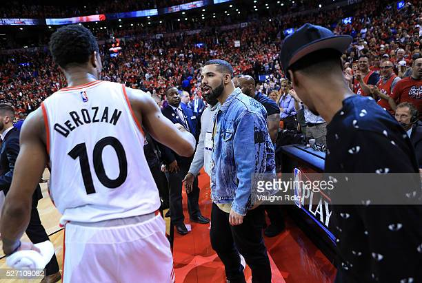 Singer Drake congratulates DeMar DeRozan of the Toronto Raptors following Game Seven of the Eastern Conference Quarterfinals against the Indiana...