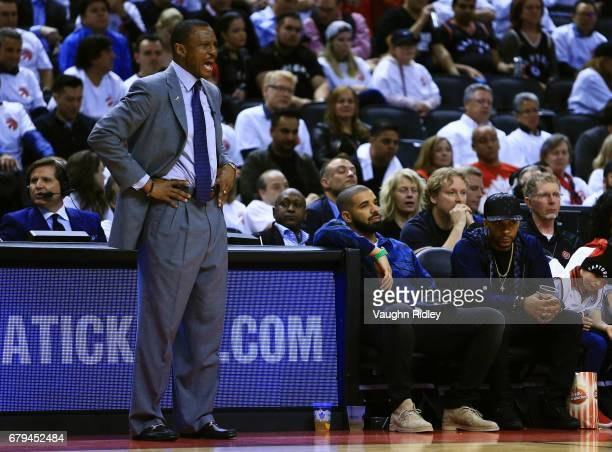 Singer Drake looks on as Head Coach of the Toronto Raptors Dwane Casey shouts to his players as Drake looks on from his seat in the second half of...
