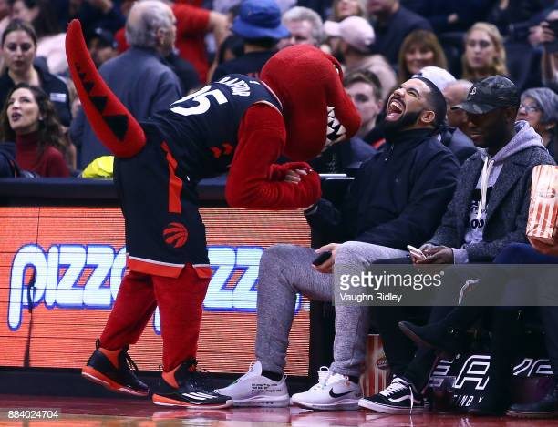 Singer Drake shares a joke with the Toronto Raptors mascot The Raptor during the first half of an NBA game against the Indiana Pacers at Air Canada...