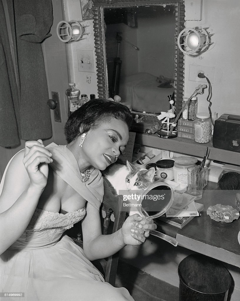 Singer Eartha Kitt, a sensation in 'New Faces of 1952,' checks here make-up as her cat 'Jinx' looks on with wide eyes. Unlike the rest of the animals backstage, 'Jinx' prefers to remain in Eartha's dressing room while the singer is on stage. It isn't that she's anti-social or that she just doesn't like the other pets--it's just that she does a lot of reading.