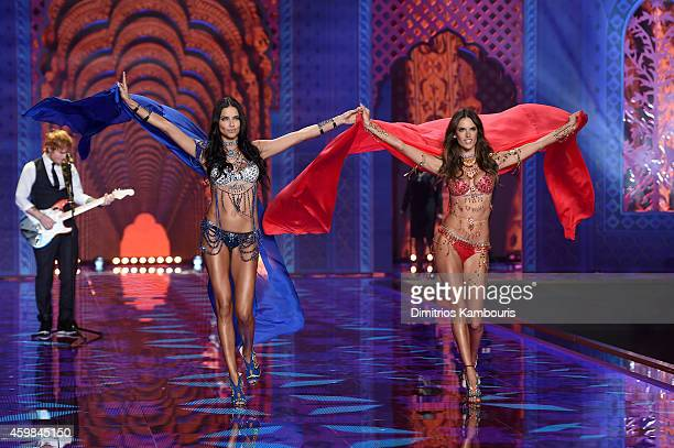 Singer Ed Sheeran performs on stage as models Adriana Lima and Alessandra Ambrosio walk the runway during the 2014 Victoria's Secret Fashion Show at...