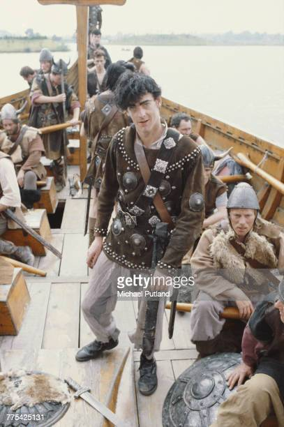 Singer Eddie Tenpole of English punk band Tenpole Tudor pictured in centre on a replica viking longboat during a video shoot for their single...