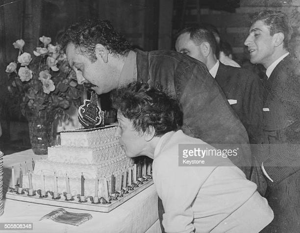 Singer Edith Piaf helping musician Georges Brassens blow out the candles on his 37th birthday cake 1958
