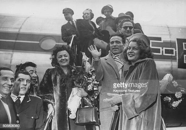 Singer Edith Piaf holding a bouquet of flowers as steps from her airplane with boxer Marcel Cerdan returning from America to France circa 1953