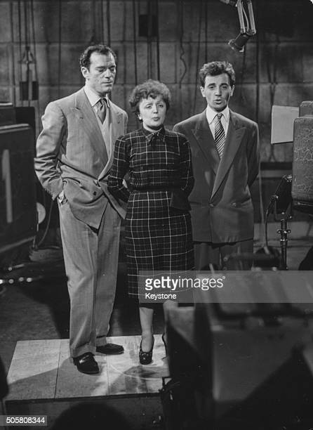 Singer Edith Piaf pictured singing in front of a camera with Eddie Constantine and Charles Aznavour as they film for a television show, Paris,...