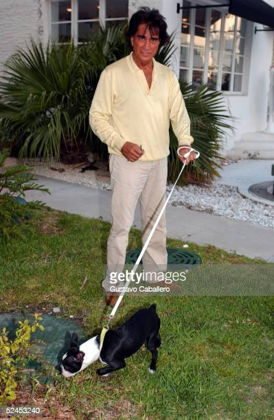 Singer El Puma walks his dog on Collins Avenue in South Beach on March 18 2005 in Miami Beach Florida