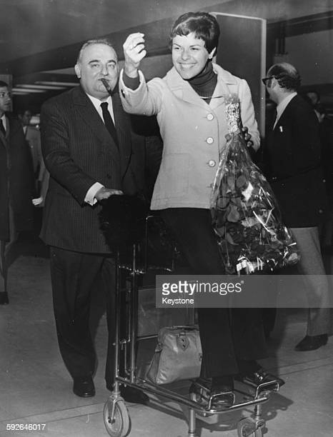 Singer Elis Regina being pushed along on a luggage trolley by Bruno Coquatrix owner and manager of the Paris Olympia Music Hall France circa 1970