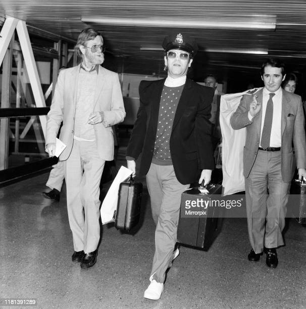 Singer Elton John arrives at Heathrow airport from his 10 week tour of the States wearing an American Policeman's hat pictured on the right is his...