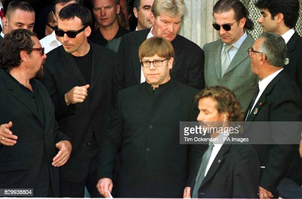 Singer Elton John leaves the memorial service for murdered fashion designer Gianni Versace with his partner David Furnish in Milan Italy