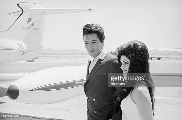 Singer Elvis Presley and his bride Priscilla Ann Beaulieu smile happily as they prepare to board a chartered jet airplane after their marriage at the...
