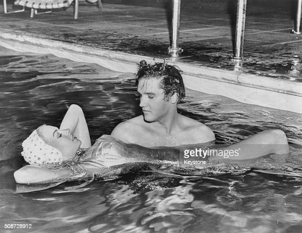 Singer Elvis Presley holding up actress Jennifer Holden his costar in the film 'Jailhouse Rock' as they spend time together in a swimming pool circa...
