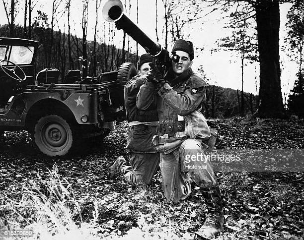 Singer Elvis Presley holds an artillery gun during his Army training.