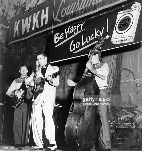 Singer Elvis Presley joins his guitar player Scotty Moore and bass player Bill Black on a weekly broadcast of 'Lousiana Hayride' at the Shreveport...