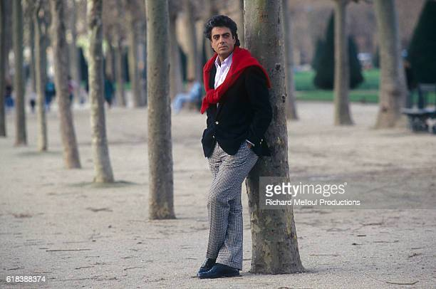 Singer Enrico Macias leans against a tree in Paris