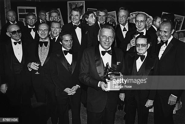 Singer Frank Sinatra holds a Grammy Awards as he is honored by celebrity friends Paul Anka Glenn Ford Phil Harris Rich Little Red Skelton Julie Styne...
