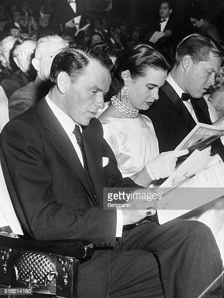 Singer Frank Sinatra looks at a program as he sits beside Gloria Vanderbilt, whom he escorted from the Ambassador Hotel to the Alvin Theatre to see...