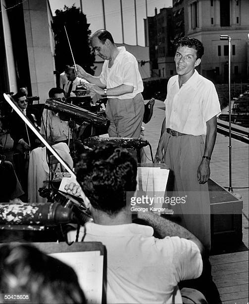 Singer Frank Sinatra rendering a song as conductor Max Steiner leads the New York Philharmonic orchestra during rehearsal of one of his popular...