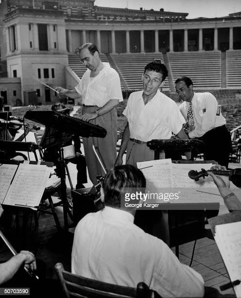 Singer Frank Sinatra rendering a song as conductor Max Steiner leads the New York Philharmonic orchestra during rehearsal for upcoming concert as the...