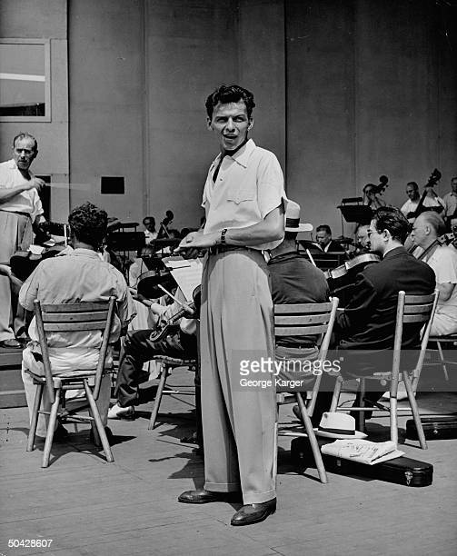 Singer Frank Sinatra singing as conductor Max Steiner begrudgingly leads the New York Philharmonic orchestra during rehearsal for the crooner's...