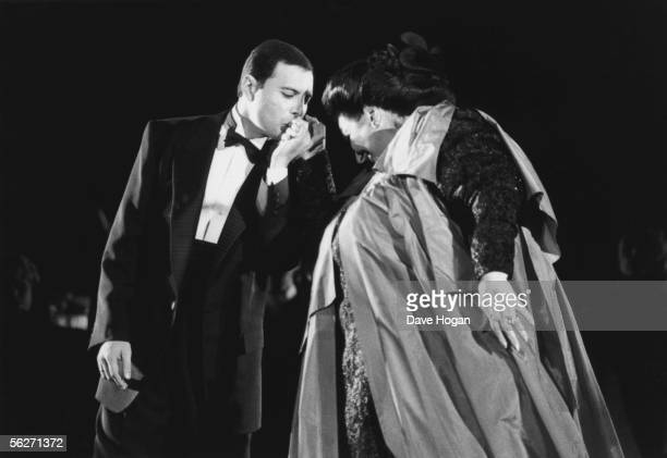 Singer Freddie Mercury kisses opera singer Montserrat Caballe on the hand as they perform 'Barcelona' at a music festival in the city to celebrate...