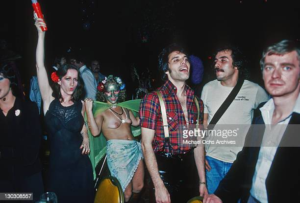 Singer Freddie Mercury of British rock band Queen with female groupies October 31st 1978