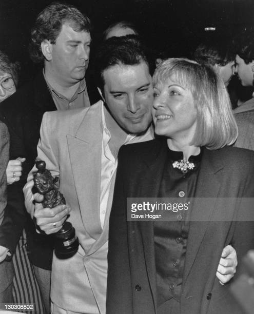 Singer Freddie Mercury of British rock band Queen with his friend Mary Austin at the Ivor Novello Awards held by the British Academy of Songwriters...