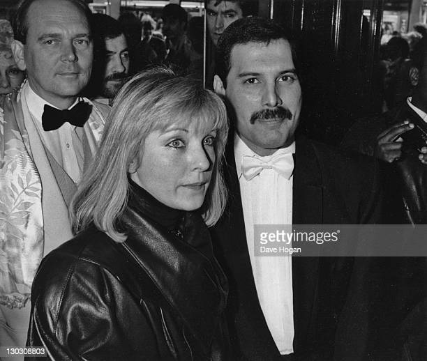 Singer Freddie Mercury of British rock band Queen with his friend Mary Austin at an afterparty in London for 'Dave Clark's Time The Musical' 9th...
