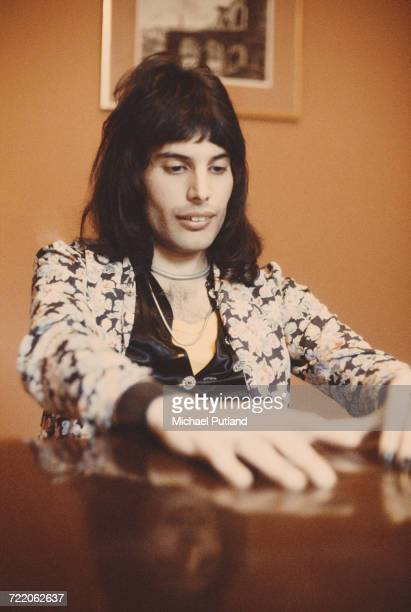 Singer Freddie Mercury of British rock group Queen pictured sitting at a table on 12th February 1974