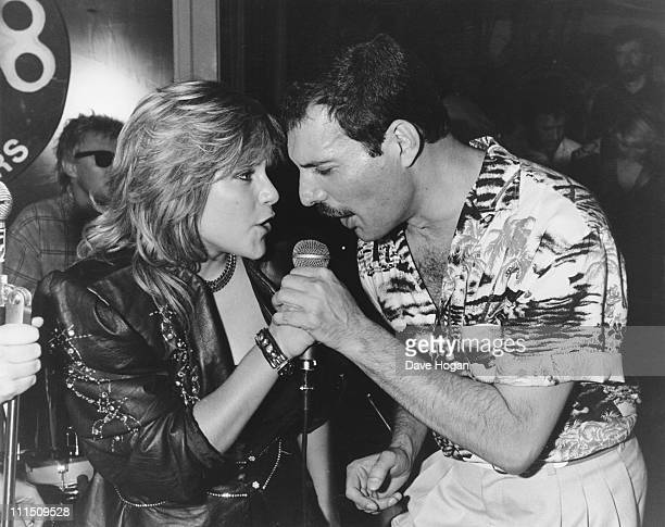 Singer Freddie Mercury of Queen performs a duet with Samantha Fox during a party at Kensington Roof Gardens in London, 12th July 1986. The event is...