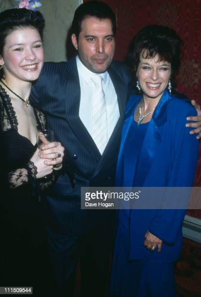 Singer Freddie Mercury of Queen with actresses Catherine Zeta Jones and Jill Gascoine at a party for the new cast of the musical '42nd Street' in...