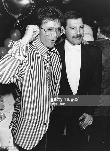 Singer Freddie Mercury of Queen with Cliff Richard at an after-party in London for 'Dave Clark's Time - The Musical', 9th April 1986.