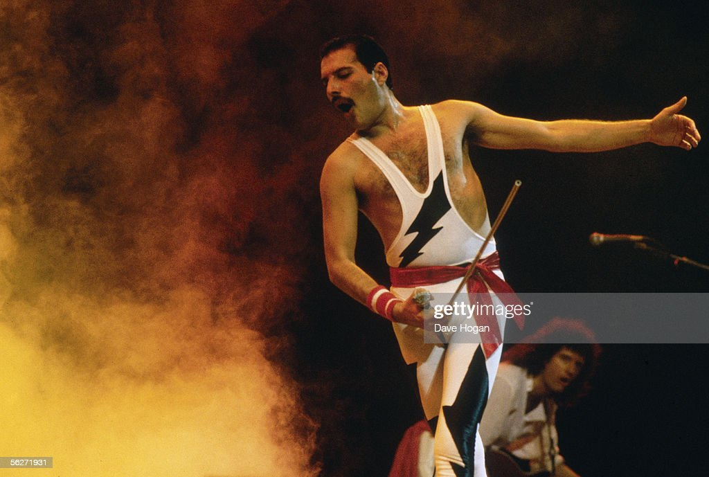 Singer Freddie Mercury performing on stage with rock group Queen, 1985. Guitarist Brian May is in the background.